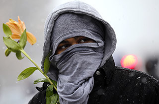A demonstrator takes part in a protest marking the 100th day since the shooting death of Michael Brown in St. Louis, Missouri November 16, 2014. A crowd of a couple hundred demonstrators, angry about the fatal August shooting of an unarmed black teenager by a white police officer, took to the streets of St. Louis on Sunday, briefly blocking a major intersection in protest. Dozens of people lay down in the street outside of a downtown theater hosting a film festival, pretending to have been shot by other protesters playing the role of police officers in an action intended to evoke the memory of 18-year-old Michael Brown, who died 100 days ago in front of his home in the suburb of Ferguson, Missouri.  REUTERS/Jim Young   (UNITED STATES - Tags: CRIME LAW CIVIL UNREST POLITICS) - RTR4ECX7