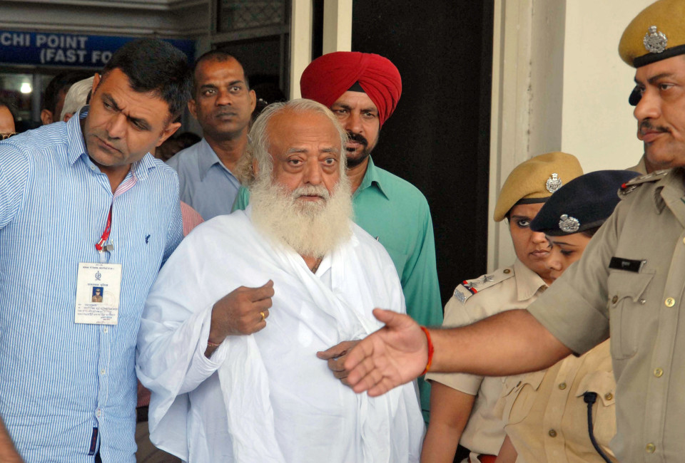 Police escort spiritual leader Asaram Bapu (C) outside an airport after his arrest in Jodhpur, in India's desert state of Rajasthan. Police arrested Bapu from India's central Madhya Pradesh state and transited him to neighbouring Rajasthan for further questioning on charges of sexual assault on a minor.