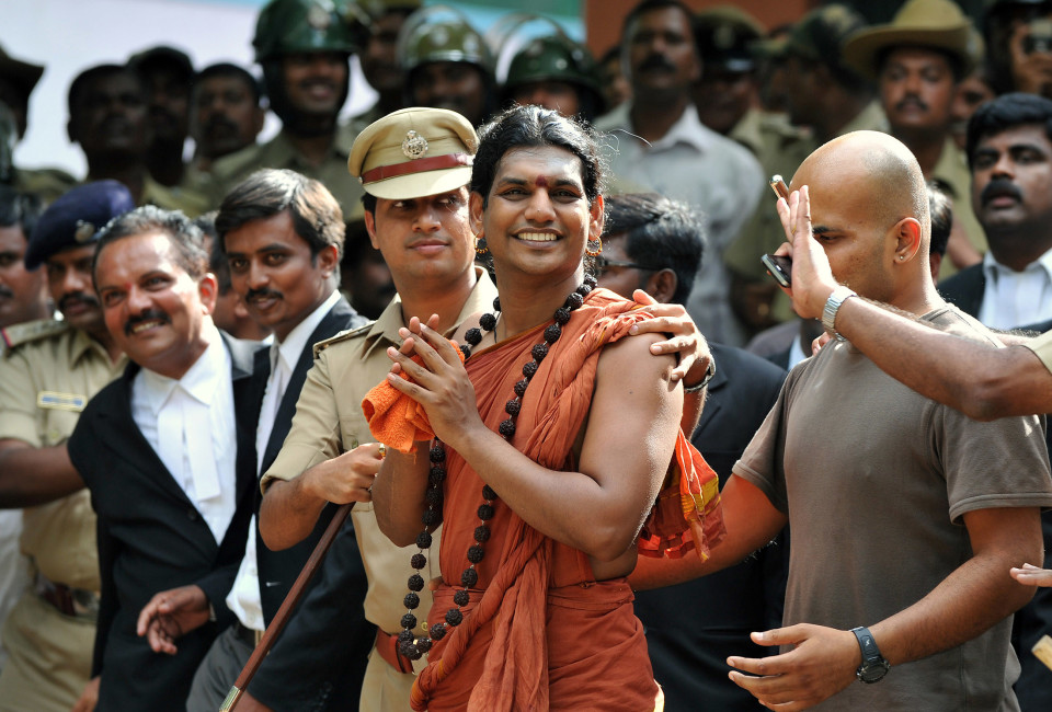 Police escort controversial Hindu Godman Swami Nityananda (C) after appearing for his bail plea at the judicial magistrate court at Ramanagar District, some 50 kms from Bangalore. A popular Indian guru facing a series of assault and sexual abuse charges was in police custody June 14 after he turned himself in to court authorities.