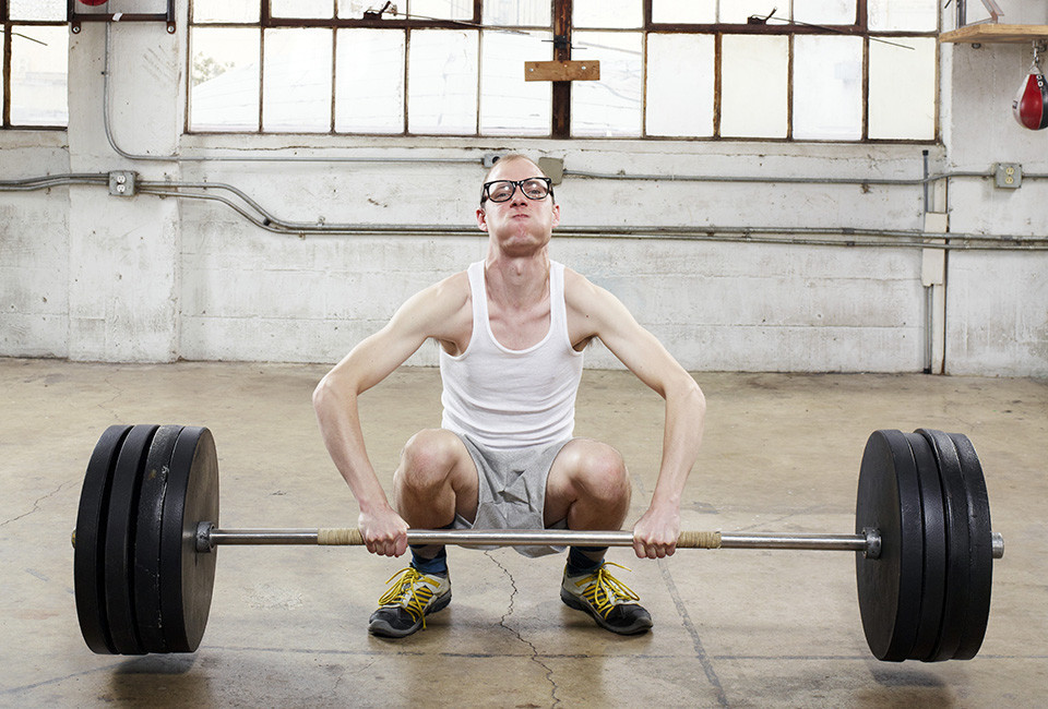 Thin intellectual about to lift heavy weight --- Image by © Tim Tadder/Corbis