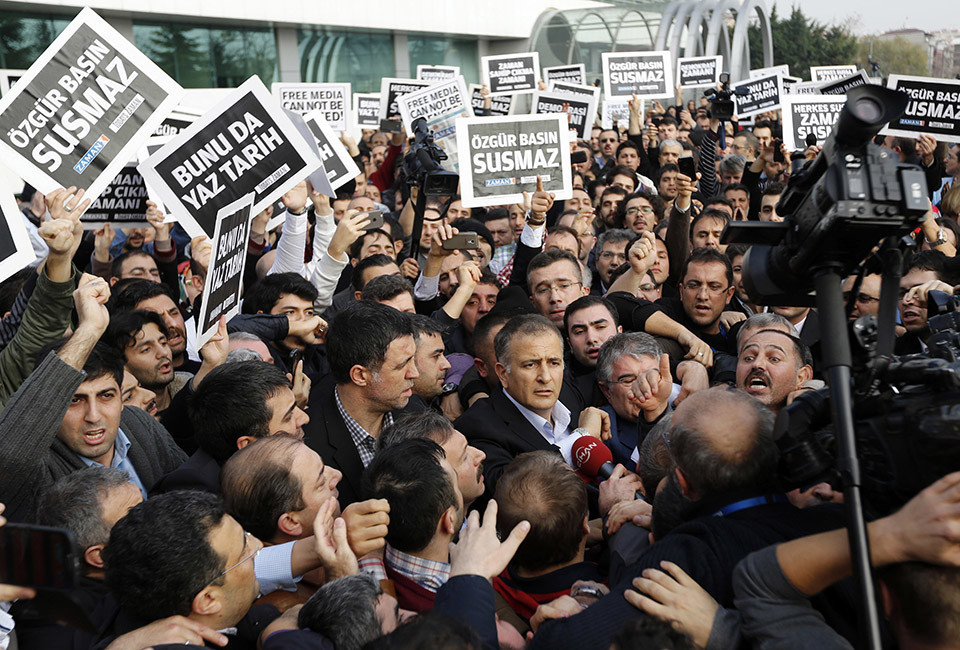 Zaman editor-in-chief Ekrem Dumanli, surrounded by his colleagues and plainclothes police officers (C), leaves the headquarters of Zaman daily newspaper in Istanbul December 14, 2014. Turkish police raided media outlets close to a U.S.-based Muslim cleric on Sunday and detained 24 people including top executives and ex-police chiefs in operations against what President Tayyip Erdogan calls a terrorist network conspiring to topple him. REUTERS/Murad Sezer (TURKEY - Tags: CRIME LAW POLITICS MEDIA) - RTR4HY9H