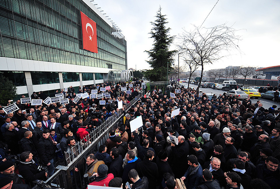 Staff members and supporters of Zaman newspaper protest against a raid by counter-terror police outside the newspaper headquarters in Istanbul on December 14, 2014. Turkish police launched a sweeping operation to arrest supporters of President Recep Tayyip Erdogan's rival, US-exiled imam Fethullah Gulen, including a raid on the offices of the Zaman daily, which is close to the cleric. A huge crowd gathered outside the offices of Zaman on the outskirts of Istanbul, creating a small stampede and forcing the police to leave the building without detaining any newspaper employees. AFP PHOTO/OZAN KOSE        (Photo credit should read OZAN KOSE/AFP/Getty Images)