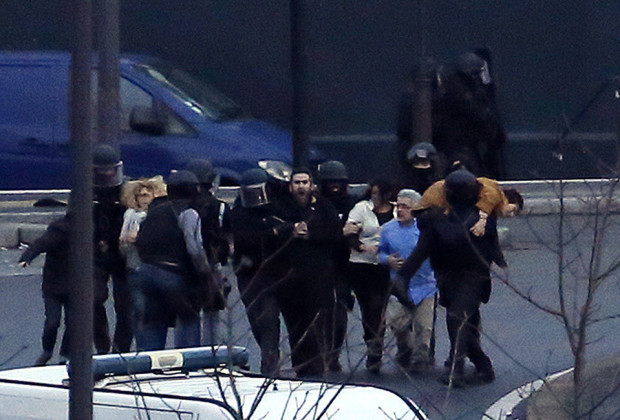 ALTERNATIVE CROP Members of the French police special forces evacuate the hostages after launching the assault at a kosher grocery store in Porte de Vincennes, eastern Paris, on January 9, 2015 where at least two people were shot dead on January 9 during a hostage-taking drama at a Jewish supermarket in eastern Paris, and five people were being held, official sources told AFP. AFP PHOTO / THOMAS SAMSON        (Photo credit should read THOMAS SAMSON/AFP/Getty Images)