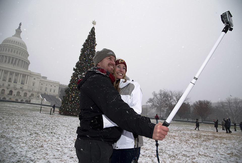 Dan Ferguson (L) and Ashley Blanton take pictures of themselves in snow flurries at the U.S. Capitol in Washington, December 8, 2013.  REUTERS/Jonathan Ernst    (UNITED STATES) - RTX16A13