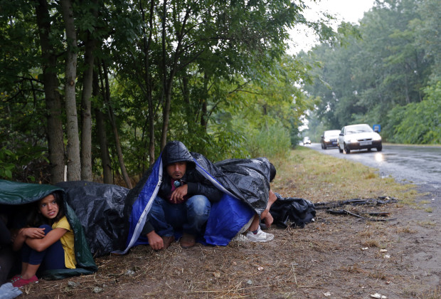 Migrants from Syria use sleeping bags to protect themselves from the rain as they rest on the side of a road after crossing the border illegally from Serbia, near Asotthalom, Hungary July 27, 2015. REUTERS/Laszlo Balogh TPX IMAGES OF THE DAY - RTX1M0R8