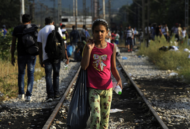 A migrant girl walks on the train tracks near the village of Idomeni at the Greek-Macedonian border, August 20, 2015. Macedonia moved to cut off the flow of migrants pouring over its southern border with Greece on Thursday, deploying riot police in armored vehicles and calling out the army under a state of emergency.  REUTERS/Alexandros Avramidis  - RTX1OZJV