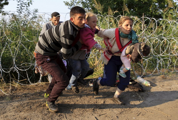 Syrian migrants run after crossing under a fence as they enter Hungary, at the border with Serbia, near Roszke, August 27, 2015. Hungary made plans on Wednesday to reinforce its southern border with helicopters, mounted police and dogs, and was also considering using the army as record numbers of migrants, many of them Syrian refugees, passed through coils of razor-wire into Europe. REUTERS/Bernadett Szabo - RTX1PU4V