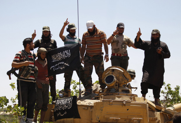 Islamist Syrian rebel group Jabhat al-Nusra members gesture while posing on a tank on Al-Khazan frontline of Khan Sheikhoun, northern Idlib province May 17, 2014. REUTERS/Hamid Khatib (SYRIA - Tags: CIVIL UNREST MILITARY POLITICS CONFLICT) - RTR3PM9N