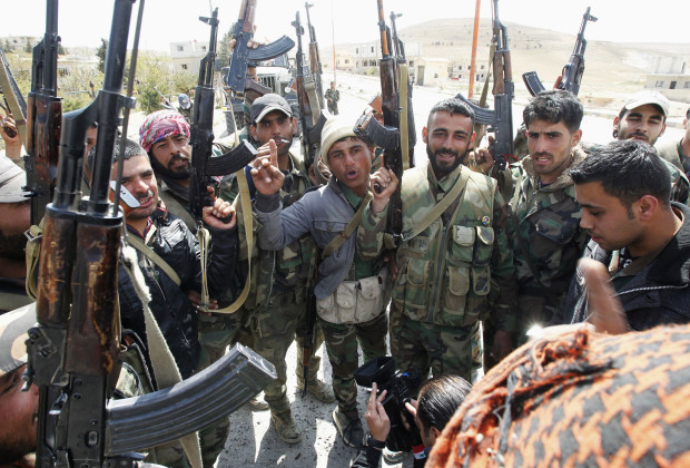 Soldiers loyal to Syria's President Bashar al-Assad pose with their weapons as they celebrating taking control of al-Sakhra village in Qalamoun Mountains, northeast of Damascus April 14, 2014. Syrian soldiers backed by Hezbollah fighters recaptured the town of Maaloula, north of Damascus, on Monday, military sources and state television said, further squeezing rebels' supply routes through the Qalamoun mountains into Lebanon.   REUTERS/Khaled al-Hariri (SYRIA - Tags: MILITARY POLITICS CONFLICT CIVIL UNREST) - RTR3L99Q
