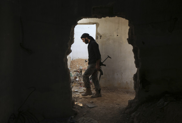 A fighter from the Free Syrian Army's Al Rahman legion carries his weapon as he moves inside a damaged building on the frontline against the forces of Syria's President Bashar al-Assad in Jobar, a suburb of Damascus, Syria July 27, 2015. REUTERS/Bassam Khabieh - RTX1M0CH