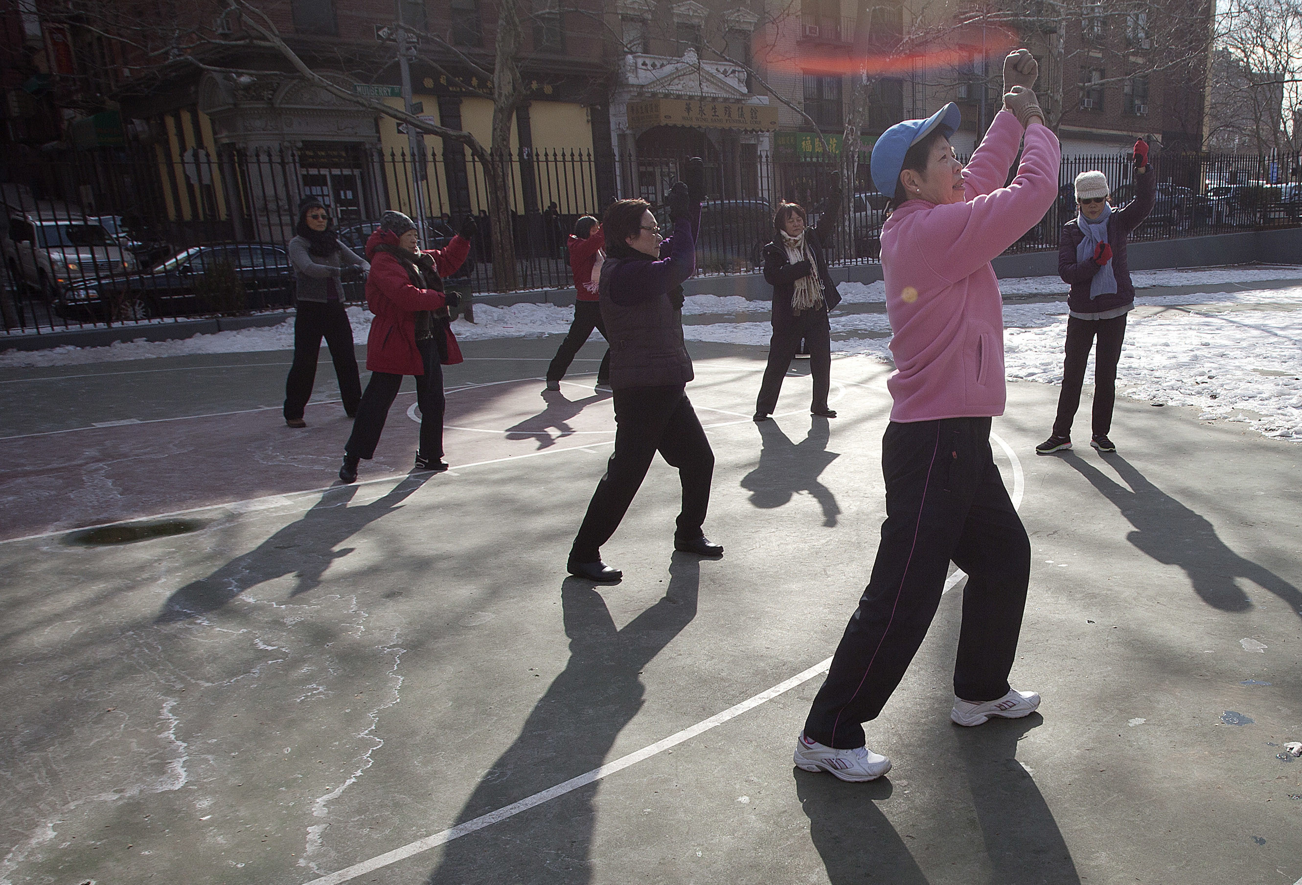 Women exercise in a park in Chinatown in the Manhattan Borough of New York March 5, 2014. REUTERS/Carlo Allegri (UNITED STATES - Tags: SOCIETY) - RTR3G2MZ