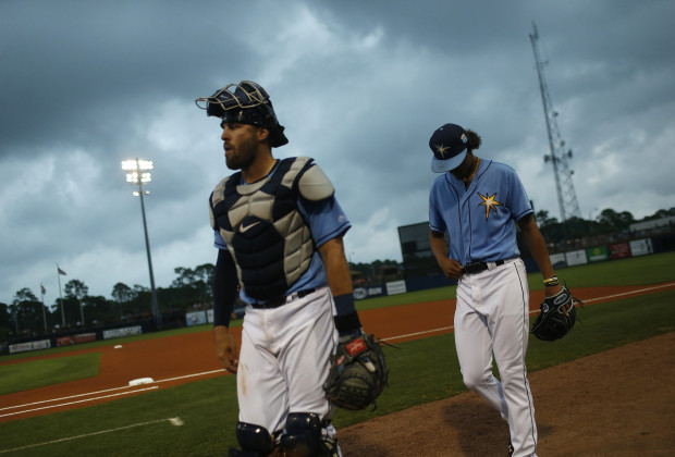 PORT CHARLOTTE, FL - MARCH 19:  Catcher Curt Casali #19 of the Tampa Bay Rays and pitcher Chris Archer #22 make their way toward the dugout before the start of an MLB spring training game against the Baltimore Orioles on March 19, 2016 at Charlotte Sports Park in Port Charlotte, Florida.  The game was later canceled due to weather. (Photo by Brian Blanco/Getty Images) *** Local Caption *** Curt Casali; Chris Archer