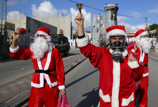 Palestinian protesters wearing Santa Claus costumes take part in an anti-Israel protest in front of the Israeli barrier in the West Bank city of Bethlehem December 18, 2015. REUTERS/Ammar Awad  - RTX1Z9DR