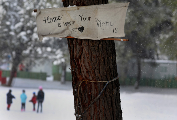 "A banner reading: ""Home is where your mom is"" is attached to a tree as stranded Syrian refugee children walk through a snowstorm at a refugee camp north of Athens, Greece January 10, 2017.REUTERS/Yannis Behrakis - RTX2YCDT"