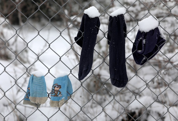 Socks that belong to stranded refugees are covered in snow as they hang on a fence during a snowstorm at a refugee camp north of Athens, Greece January 10, 2017.REUTERS/Yannis Behrakis - RTX2YCEC