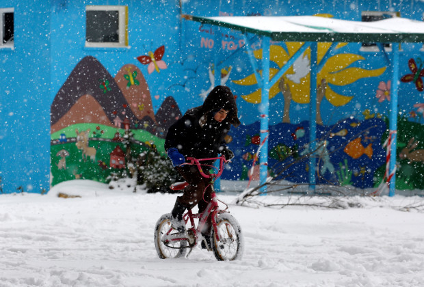 A stranded refugee boy rides his bicycle through a snowstorm at a refugee camp north of Athens January 10, 2017.REUTERS/Yannis Behrakis - RTX2YCOL