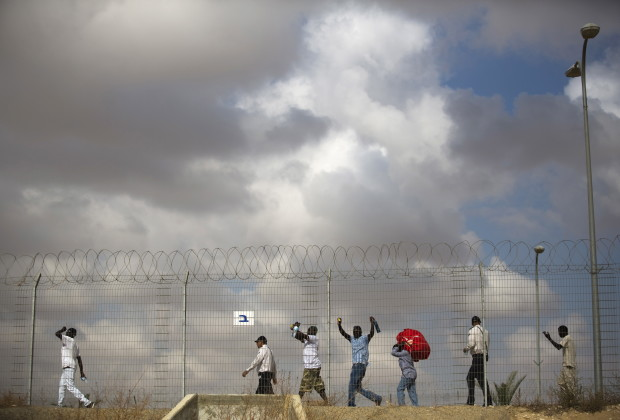 African migrants walk behind a fence as they leave Holot detention centre in Israel's southern Negev desert August 25, 2015. Israel on Tuesday began releasing some 1,200 African migrants whom it has interned for more than a year in the detention centre. Under the terms of their release, they are banned from living or working in Tel Aviv and the southern resort city of Eilat, which both have large migrant communities. Two weeks ago, Israel's Supreme Court reduced from 20 months to 12 months the period of time illegal migrants could be held in custody pending the outcome of their requests for asylum. An estimated 47,000 African migrants live in Israel, and many of them are seeking asylum. Israel has recognized only a handful of such claims. REUTERS/Amir Cohen - RTX1PJWJ