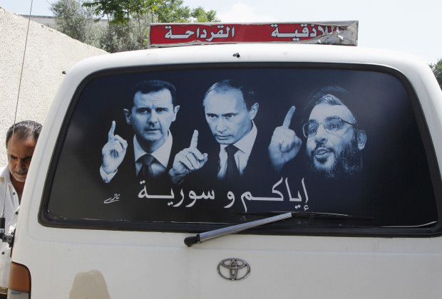 A poster showing Syrian President Bashar al-Assad (L), Russian President Vladimir Putin (C) and Lebanese Hezbollah leader Sayyed Hassan Nasrallah is seen on a micro bus in al-Qardahah town, near Latakia city May 26, 2014. Syria is preparing to hold presidential elections on June 3 that looks all but certain to give President Assad a third seven-year term. Al-Qardahah town is the home town of Assad. REUTERS/Khaled al-Hariri (SYRIA - Tags: POLITICS CONFLICT CIVIL UNREST ELECTIONS TRANSPORT) - RTR3QZI9