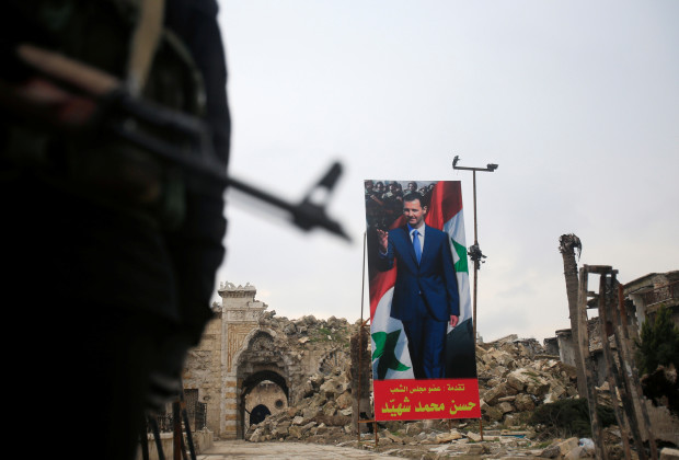 A Syrian army soldier stands guard as a poster depicting Syria's President Bashar al-Assad is seen in the background in the Old City of Aleppo, Syria January 31, 2017. REUTERS/Ali Hashisho - RTX2Z1F6