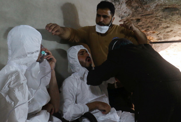 A man breathes through an oxygen mask as another one receives treatments, after what rescue workers described as a suspected gas attack in the town of Khan Sheikhoun in rebel-held Idlib, Syria April 4, 2017. REUTERS/Ammar Abdullah - RTX33ZB6
