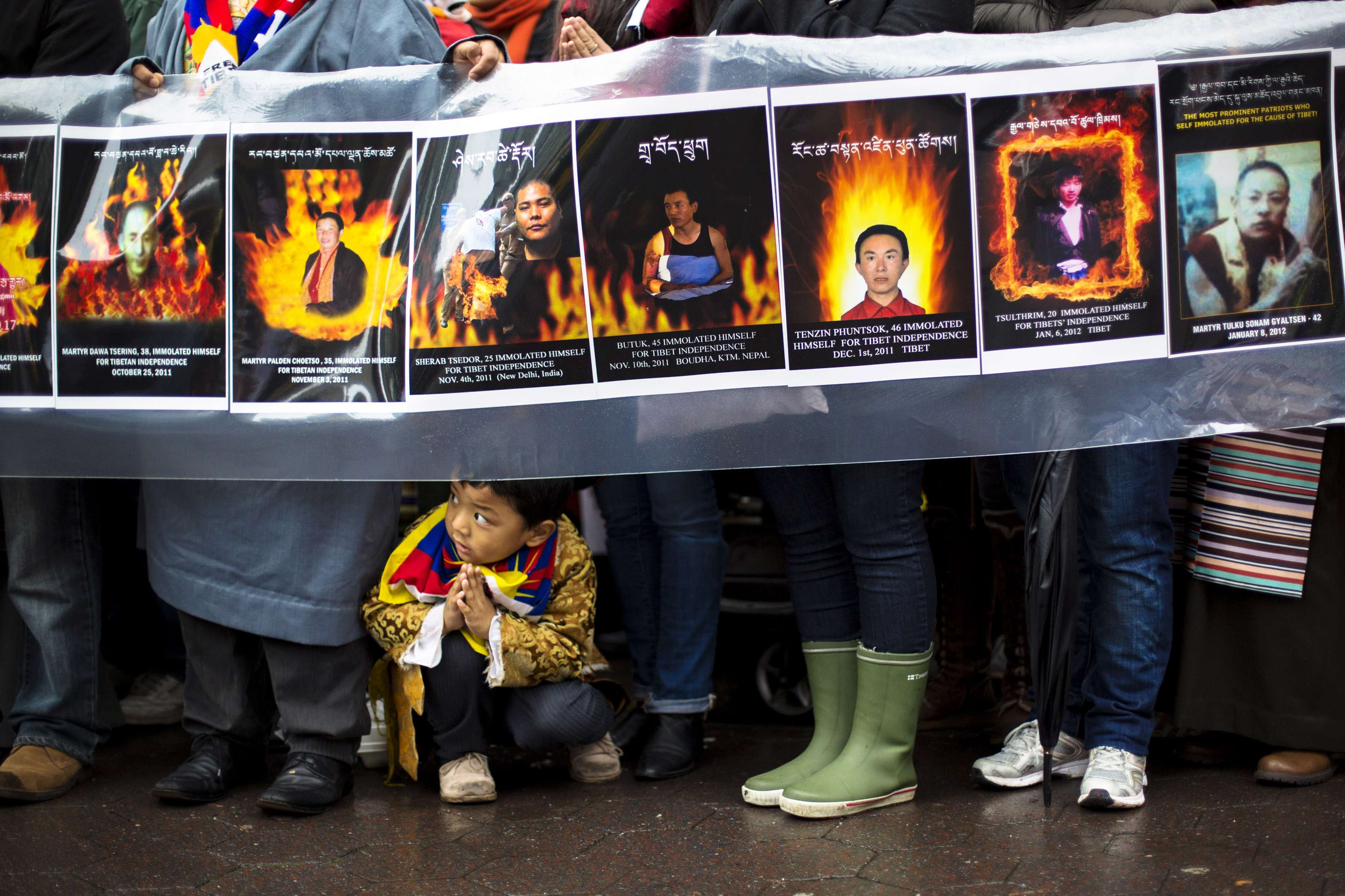 A child gestures at feet of protesters during solidarity march from Chinese Consulate to UN Headquarters in support of Tibet in New York