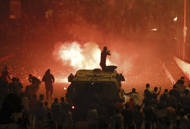 10 Oct 2013, Cairo, Egypt --- A riot police officer, on a armoured personnel carrier surrounded by anti-Mursi protesters (foreground), fires rubber bullets at members of the Muslim Brotherhood and supporters of ousted Egyptian President Mohamed Mursi along a road at Ramsis square, which leads to Tahrir Square, during clashes at a celebration marking Egypt's 1973 war with Israel, in Cairo in this October 6, 2013 file photo. To match Special Report EGYPT-INTERIOR/ REUTERS/Amr Abdallah Dalsh/Files (EGYPT - Tags: POLITICS CIVIL UNREST) --- Image by © AMR ABDALLAH DALSH/Reuters/Corbis