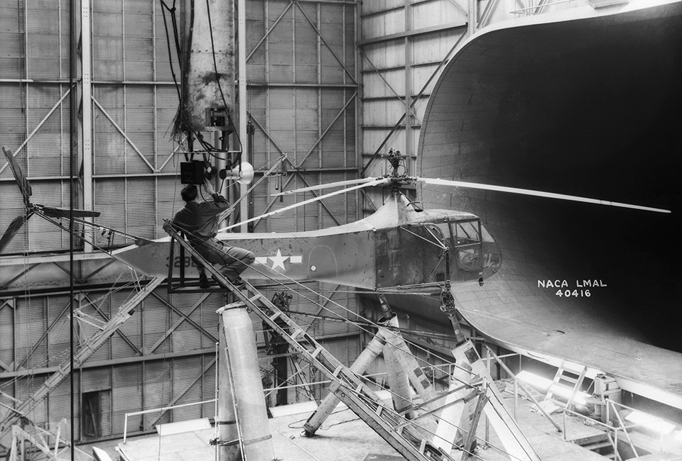 One of Langley's Sikorsky YR-4B/HNS-1 helicopters is seen in the 30 x 60 Full Scale Tunnel. The technician is setting up camera equipment for stopped-action rotor-blade photos. Sikorsky built hundreds of R-4 helicopters during World War II. It was the first mass-produced helicopter.