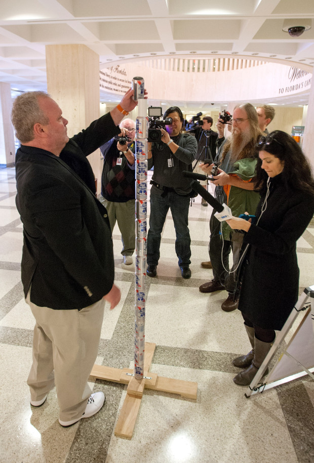 TALLAHASSEE, FL - DECEMBER 11: Chaz Stevens from Deerfield Beach, Florida assembles his Festivus pole out of beer cans in the rotunda of the Florida Capitol as the media looks on December 11, 2013 in Tallahassee, Florida.  Stevens display was intended to counter the religious Christian Nativity manger on display. Based on an episode of the television sitcom Seinfeld, Festivus has become a secular holiday celebrated on December 23 to represent the antithesis of the commercialism of the Christmas season. (Photo by Mark Wallheiser/Getty Images)