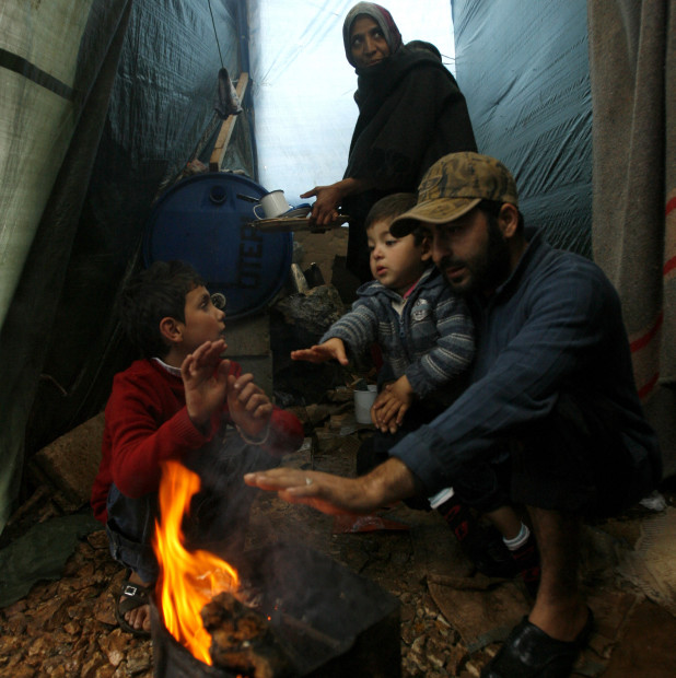 A Syrian refugee family use firewood to stay warm during rainfall in a refugee camp in the village of Ketermaya, southeast of Beirut, on December 11, 2013. Thousands of Syrian refugees living in makeshift camps in Lebanon were weathering a winter storm that brought snow, rain and freezing temperatures to the country. AFP PHOTO/MAHMOUD ZAYYAT        (Photo credit should read MAHMOUD ZAYYAT/AFP/Getty Images)