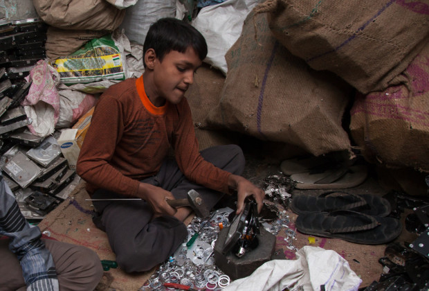 """New Delhi: India: 2013 As this 12 year old boy hammers a drive, tiny screws and shards of copper were flying. """"These will be made into kitchen utensils"""""""