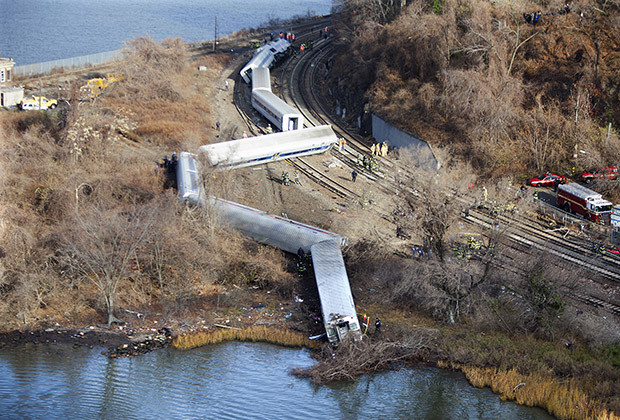 Emergency workers examine the site of a Metro-North train derailment in the Bronx borough of New York December 1, 2013. At least four people were killed and 63 injured, including 11 critically, when the suburban train derailed, with at least five cars from the Metro-North train sliding off the tracks, officials said.  REUTERS/Carlo Allegri (UNITED STATES - Tags: TRANSPORT DISASTER) - RTX1601L