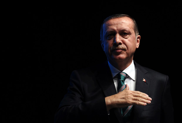 Turkish prime minister Recep Tayyip Erdogan stands on stage after a speech at the end of a ceremony marking the anniversary of the death of Jelaleddin Mevlana Rumi, Sufi mystic, poet and founder of the sufism, on December 13,2013, at Ulker Sports Arena in Istanbul. The dervishes are adepts of Sufism, a mystical form of Islam that preaches tolerance and a search for understanding. Those who whirl, like planets around the sun, turn dance into a form of prayer. Some say the whirling dervishes belong more to the central, conservative city of Konya, where the father of Sufism, Mevlana Jalaluddin Rumi, lived in the 13th century, than to the cosmopolitan modern city. AFP PHOTO / OZAN KOSE