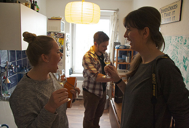 Anni Kralisch-Pehlke, left, and Jule Müller, right, conduct an informal taste test of Sebastian Ruchay's favorite single malt whisky, Springbank 15. The result leaves Anni breathing fire as Müller laughs and Ruchay puts away the scotch in the background.