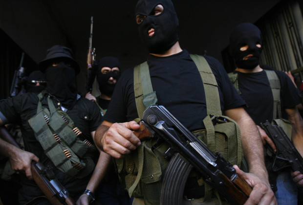 Lebanese masked gunmen from the al-Muqdad clan ready to speak to the press in Beirut's southern suburbs on August 15, 2012. The Muqdads, a large Lebanese Shiite Muslim clan, said it has kidnapped at least 20 Syrians to try to secure the release of a family member abducted near Damascus this week. AFP PHOTO/STR        (Photo credit should read -/AFP/GettyImages)