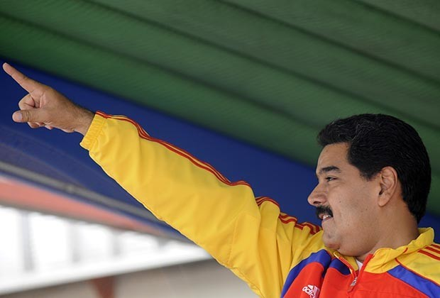"""Venezuelan President Nicolas Maduro greets supporters as he arrives to take part in the """"Great day for peace"""", an activity organized by the Venezuelan government as part of its fight against violence, in Caracas on January 26, 2014. Thousands of Venezuelans marched on Sunday in several cities to protest against violence in Venezuela, one of the most violent countries in South America."""