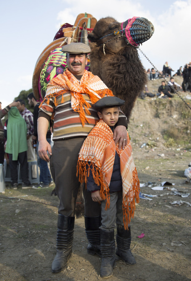 Omer Aksoy posing with his grandson Ayberk Mujdat, 9, in front of their camel at the Selcuk Efes Camel Wrestling Festival. Many enthusiasts dress in traditional nomadic clothing including special accordion boots, shawls and caps. Photo by Jodi Hilton/Vocativ