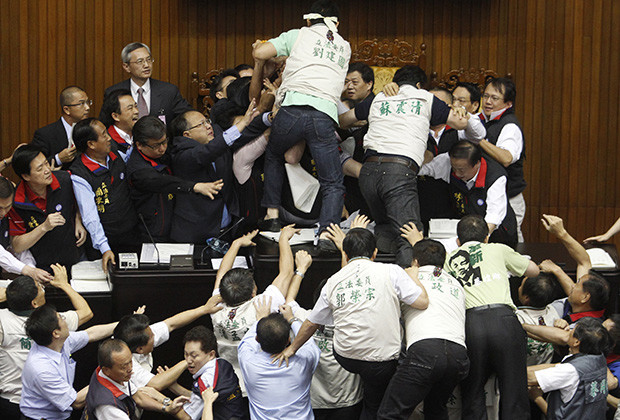 Opposition Democratic Progressive Party (DPP) legislators scuffle with ruling Nationalist Party (KMT) legislators (top) at the Legislative Yuan in Taipei July 8, 2010. Taiwan legislators threw objects, splashed water and kicked one another on Thursday, sending two to the hospital in a brawl over how fast to ratify a trade pact with China that is shaping up as a pivotal election issue.   REUTERS/Nicky Loh (TAIWAN - Tags: POLITICS CIVIL UNREST) - RTR2G7J9