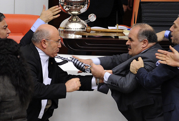 Turkey's ruling AK Party (AKP) lawmaker Muhittin Aksak (R) and main opposition Republican People's Party (CHP) lawmaker Mahmut Tanal (L) scuffle during a debate at the parliament in Ankara late February 8, 2012. REUTERS/Stringer (TURKEY - Tags: POLITICS CIVIL UNREST) - RTR2XIJE
