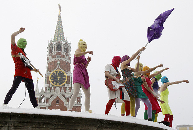 Members of the Russian radical feminist group 'Pussy Riot' sing a song at the so-called Lobnoye Mesto (Forehead Place), long before used for announcing Russian tsars' decrees and occasionally for carrying out public executions, in Red Square in Moscow January 20, 2012. Eight activists, who were later detained by police, staged a performance to protest against the policies conducted by Prime Minister Vladimir Putin.      REUTERS/Denis Sinyakov  (RUSSIA - Tags: POLITICS CIVIL UNREST SOCIETY) - RTR2WK7G