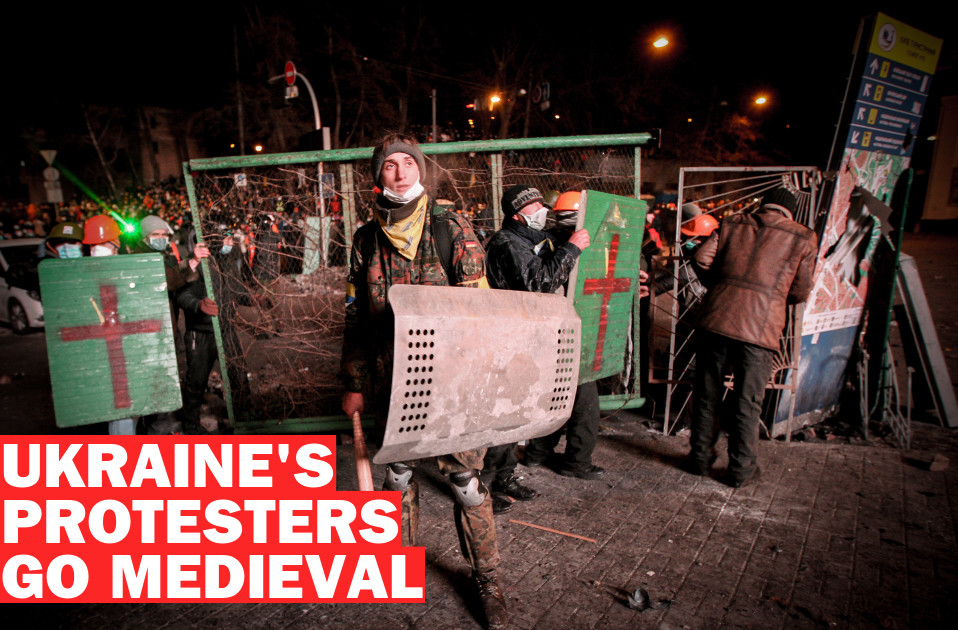 Pro-European integration protesters take cover behind shields during clashes with Ukrainian riot police in Kiev January 20, 2014. Protesters attacked riot police with sticks in Kiev on Sunday and tried to overturn a bus blocking their path to parliament, as up to 100,000 Ukrainians massed in defiance of sweeping new laws aimed at stamping out anti-government demonstrations. REUTERS/Valentyn Ogirenko (UKRAINE - Tags: POLITICS CIVIL UNREST CRIME LAW) - RTX17LZQ