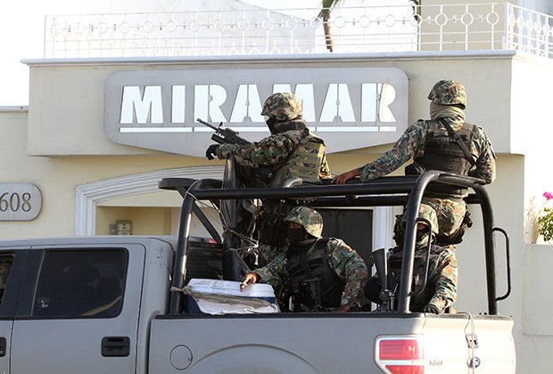 "Military personnel stand atop a truck outside the Miramar building during a raid in Mazatlan February 22, 2014. Mexico's most wanted man, drug kingpin Joaquin ""Shorty"" Guzman, has been captured in Mexico by U.S. and Mexican law enforcement officials, a U.S. government source confirmed on Saturday. According to local media, Guzman was arrested early Saturday morning during a raid at the building."