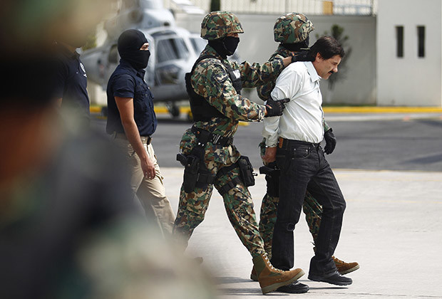 "Joaquin ""Shorty"" Guzman (R) is escorted by soldiers during a presentation at the Navy's airstrip in Mexico City February 22, 2014. Mexico has captured its most wanted man, drug kingpin Guzman, President Enrique Pena Nieto said via Twitter on Saturday, in a major victory in a long, grisly fight against drug gangs. Guzman, known as ""El Chapo"" (Shorty) in Spanish, runs Mexico's infamous Sinaloa Cartel and over the past decade emerged as one of the world's most powerful organized crime bosses."