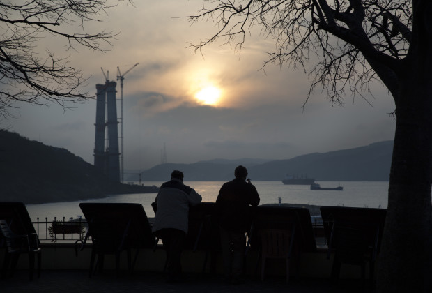 From a terrace overlooking the harbor of Poyrazkoy, a village on the Asian side of Istanbul, men take in view of the rising Third Bosphorus Bridge. It is being named Yavuz Sultan Selim after a controversial sultan who oversaw enormous expansion of the Ottoman Empire, but also the massacre of thousands of Alevi subjects. PHOTO BY JODI HILTON/VOCATIV