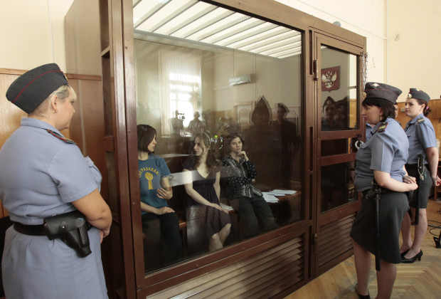"Nadezhda Tolokonnikova (L), Yekaterina Samutsevich (R) and Maria Alyokhina, members of female punk band ""Pussy Riot"", sit in the defendant's cell before a court hearing in Moscow August 8, 2012. A state prosecutor on Tuesday demanded a three-year jail term for three women from punk band Pussy Riot, saying they had abused God when they burst into a Moscow cathedral and sang a ""protest prayer"" against the Russian Orthodox Church's close links to Vladimir Putin.   REUTERS/Sergei Karpukhin (RUSSIA - Tags: POLITICS CRIME LAW CIVIL UNREST RELIGION TPX IMAGES OF THE DAY) - RTR36EWB"
