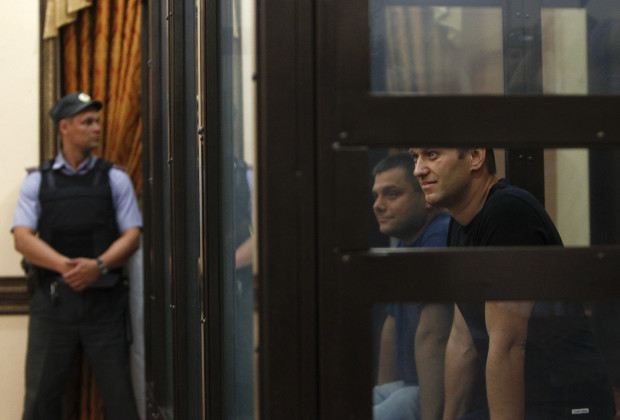 Russian opposition leader Alexei Navalny (R) and his co-defendant Pyotr Ofitserov sit inside a glass-walled cage as they attend a court hearing in Kirov, July 19, 2013. A Russian court temporarily released Navalny from custody on Friday, but placed him under travel restrictions, while he awaits the outcome of an appeal against his sentence to five years in jail. REUTERS/Sergei Karpukhin (RUSSIA - Tags: CRIME LAW POLITICS CIVIL UNREST) - RTX11RH8
