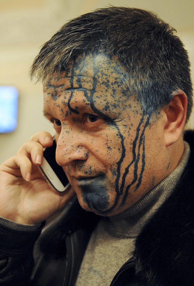 """Ukrainian opposition parliament deputy Arsen Avakov talks on his phone in a courtroom after being sprayed with green antiseptic in Kharkiv January 18, 2013. Jailed Ukrainian opposition leader Yulia Tymoshenko's trial for tax evasion was adjourned again on Friday as her defence counsel warned that her declining health had slumped to a """"critical"""" level."""