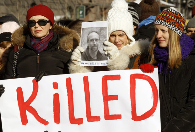 A woman holds a portrait of anti-government activist Yury Verbitsky during a flash mob to commemorate activists who were injured or killed in clashes with riot police in Kiev, February 3, 2014. According to local media, Verbitsky, who was injured during a rally in Kiev, was taken away from the hospital by unknown men. He was later found dead in the woods near Kiev Borispol airport with signs of torture. Several hundred people took part in the flashmob.