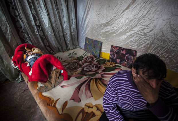 Besim sits on the mattress in his shack at Liqeni while his baby daughter lays swaddled nearby. They live in a Roma camp near Tirana's artificial lake and city park. PHOTO BY JODI HILTON
