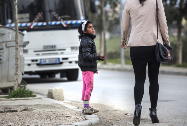 A Roma child in Tirana, Albania, begs for money from a passerby. PHOTO BY JODI HILTON