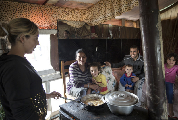 Reshat Nuredini's daughter cooks eggs in their shack in the Liqeni Roma camp in Tirana. Three generations of family share one room. PHOTO BY JODI HILTON